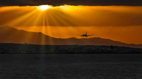 silhouette of airplane over body of water
